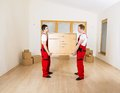 Movers in new house with lot of boxes behind them Stock Image