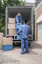 Movers unloading a moving van passing a cardboard box Stock Photos