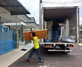Movers unloading a moving van passing cardboard box Royalty Free Stock Images
