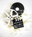 Movie clapper on mm cinema reels with unrolled filmstrip neutral background Royalty Free Stock Photography