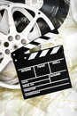Movie clapper on mm cinema reels unrolled filmstrip white background vertical Stock Photos
