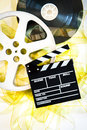 Movie clapper on mm cinema reels unrolled yellow filmstrip white background vertical Stock Photography