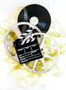 Movie clapper on mm yellow unrolled film and cinema reels neutral background vertical frame Royalty Free Stock Photo