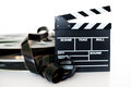 Movie clapper and vintage mm film cinema reel on white background filmstrip unrolled selective focus Stock Photography
