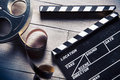 Movie slate and film reel on wood Royalty Free Stock Photo