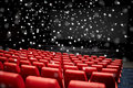 Movie theater or cinema empty auditorium entertainment and leisure concept with red seats over snowflakes Royalty Free Stock Photos