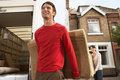 Moving couple unloading sofa from truck smiling young in front of new house Stock Photos