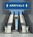 Moving escalator stairs in airport, arrivals sign Royalty Free Stock Photo