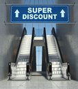 Moving escalator stairs in mall, super discount sign Stock Images