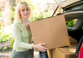 Moving on out woman loading boxes into car Royalty Free Stock Images