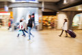 Moving people at a station in motion blur in the shopping area of railway Royalty Free Stock Photo