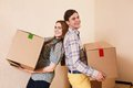 Moving to a new apartment beautiful young couple standing close each other and smiling at camera while holding cardboard boxes Royalty Free Stock Photo