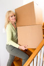 Moving on up woman boxes the stairs in a house Royalty Free Stock Photo