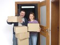 Moving in young happy couple into their new house standing the door frame with cardboard boxes Royalty Free Stock Photography