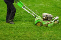 Mowing the grass a worker maintains lawn using lawnmower Stock Photo