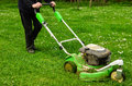 Mowing the lawn gardener green grass with push mower Stock Photo
