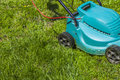 Mowing a lawn with mower Stock Photos