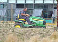 Mowing the lawn this photo shows gardener sitting on an industrial mower this photo could be used to promote industrial mowers Stock Image