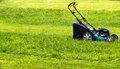 Mowing lawns. Lawn mower on green grass. mower grass equipment. mowing gardener care work tool. close up view. sunny day. Royalty Free Stock Photo