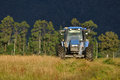 Mowing pasture tractor for silage west coast south island new zealand Royalty Free Stock Photo
