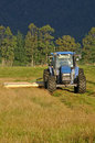 Mowing pasture tractor for silage west coast south island new zealand Stock Image