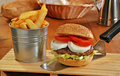 Mozzarella cheese burger an fried potatoes on rustic ambient Royalty Free Stock Image
