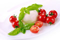 Mozzarella tomatoes basil cherry on a white plate Stock Photos