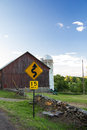 Mph sign barn yellow dangerous curve in front of a with silo Royalty Free Stock Images
