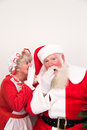 Mrs claus tells santa a secret whispers into s ear Stock Images
