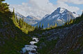 Mt fougner near m gurr lake bella coola bc canada stream running between hills and mountains with melting snow Royalty Free Stock Photo