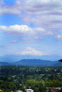 Mt hood on horizon and it s foot hills towers the under blue skies and fluffy clouds in oregon trees and a community in the Royalty Free Stock Images