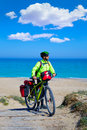 Mtb biker bicycle touring on a beach with pannier racks and saddlebag Stock Images