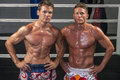 Muay thai match two caucasian fighters pose without shirts in the ring as they flex their muscles Royalty Free Stock Photo