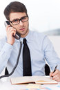 It is so much work to do confident young man in shirt and tie talking on the mobile phone and looking at camera while sitting at Royalty Free Stock Photo