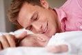 Muchacha de playing with baby del padre como mienten en cama juntos Foto de archivo