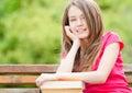 Muchacha del estudiante que se sienta en banco y la sonrisa Imagen de archivo