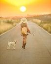 Muchacha del país que recorre abajo de un camino de la puesta del sol Imagen de archivo libre de regalías
