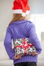 Muchacha en santa hat hiding christmas gift detrás Imagenes de archivo