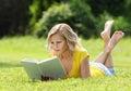 Muchacha que lee el libro mujer joven hermosa rubia con el libro que miente en la hierba al aire libre día soleado Imagenes de archivo