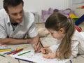 Muchacha y padre coloring book together en piso Fotos de archivo libres de regalías