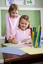 Muchachas de la escuela que escriben en cuaderno en sala de clase Foto de archivo libre de regalías