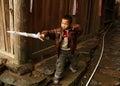 Muchacho de cinco años chino que juega con una espada plástica en la calle del pueblo imágenes editoriales Foto de archivo libre de regalías