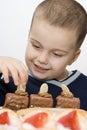 Muchacho feliz de comer las tortas Fotos de archivo libres de regalías