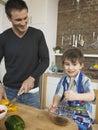 Muchacho y padre felices cooking food together en cocina Imagen de archivo