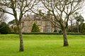 Muckross house in the killarney national park with trees and lawn visible foreground Royalty Free Stock Images