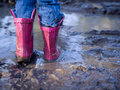 Mud puddle fun pink muddy boots Royalty Free Stock Image