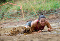 Mud run race smiling female participant crawls under the wires at a pit dash of the titans dallas texas Stock Photo