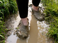 Muddy rubbers walking through the rain puddle in the Stock Photo