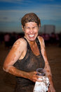 Muddy runner a woman laughs after completing a obstacle fun run she is from head to toe but is obviously happy Royalty Free Stock Image