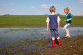 Muddy two kids walking trough a puddle Stock Image